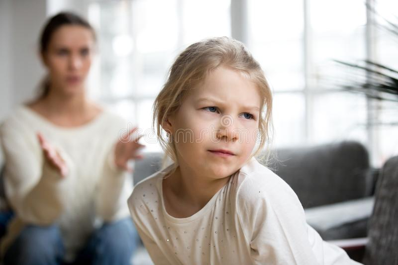 Muchacha ofendida enojada malhumorada del niño que pone mala cara ignorando a la madre que regaña h foto de archivo
