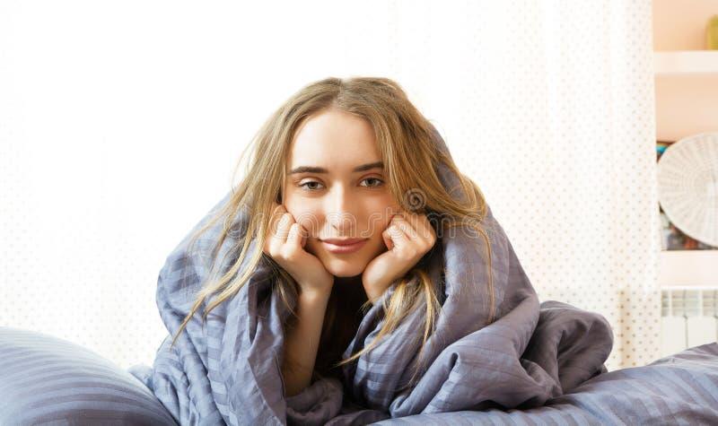 Muchacha so?olienta por la ma?ana en cama, el dormir hermoso joven de la mujer envuelto en una manta Mujer so?olienta de la belle fotografía de archivo