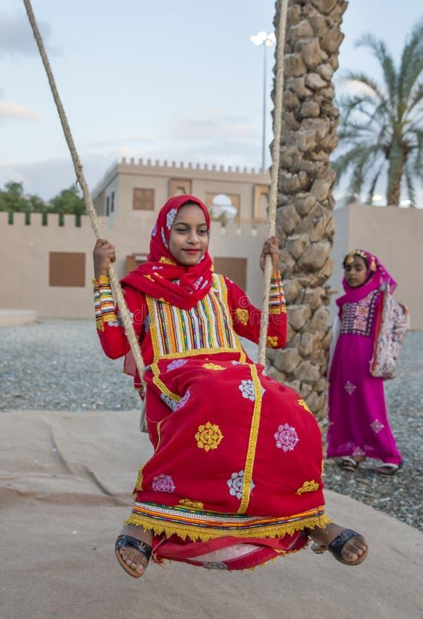 muchacha omaní en ropa tradicional en un oscilación imagen de archivo