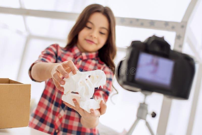 Muchacha optimista que muestra el modelo del cráneo del dinosaurio a la cámara fotografía de archivo