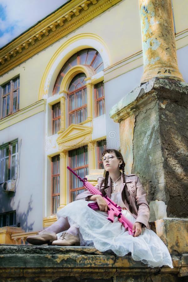 Muchacha orgullosa con un rifle en un edificio abandonado fotos de archivo