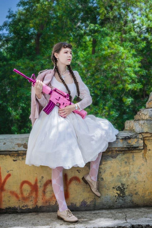 Muchacha orgullosa con un rifle en un edificio abandonado imagen de archivo