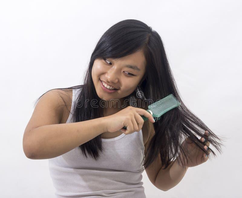 Muchacha oriental sonriente que cepilla su pelo imagen de archivo libre de regalías
