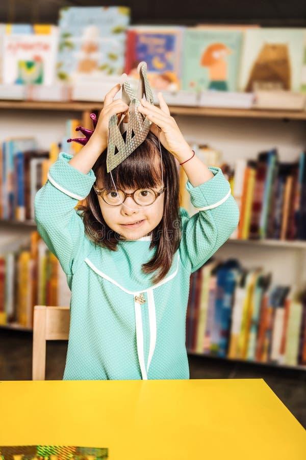 muchacha Oscuro-cabelluda con Síndrome de Down que sostiene poca corona fotos de archivo