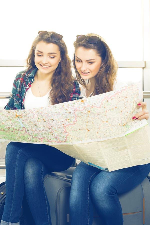 Muchacha oscuro-cabelluda joven dos que mira el mapa imagen de archivo