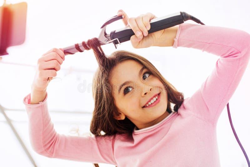 Muchacha oscuro-cabelluda linda hermosa que se encrespa el pelo mientras que consigue listo para el partido de la escuela fotografía de archivo libre de regalías