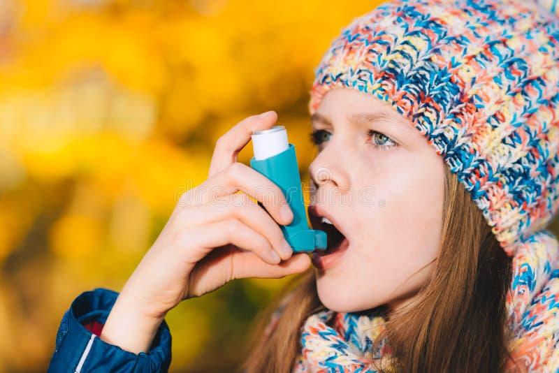 Muchacha paciente del asma que inhala la medicación para tratar la brevedad o fotos de archivo libres de regalías