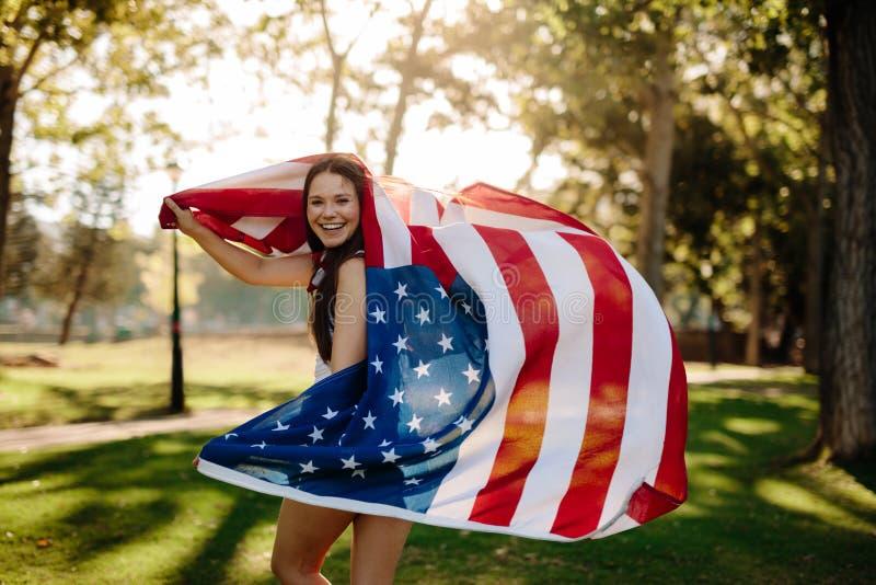 Muchacha patriótica con la bandera americana en el parque imágenes de archivo libres de regalías