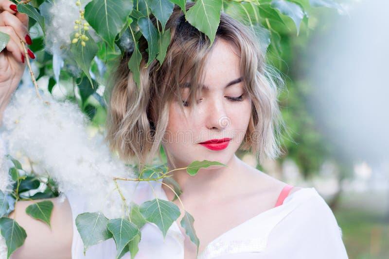 Muchacha pecosa atractiva joven que presenta cerca de árbol con la pelusa polar, labios rojos imágenes de archivo libres de regalías