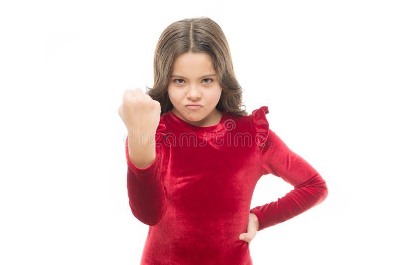 Muchacha peligrosa Sienta mi poder Niño de la muchacha que amenaza con el puño aislado en blanco Genio fuerte El amenazar con imágenes de archivo libres de regalías