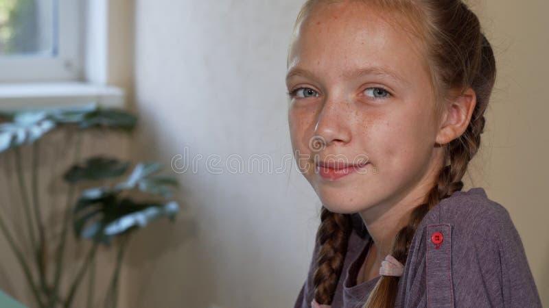 Muchacha pelirroja adorable con las pecas que sonríe y que dibuja en la escuela imagen de archivo libre de regalías