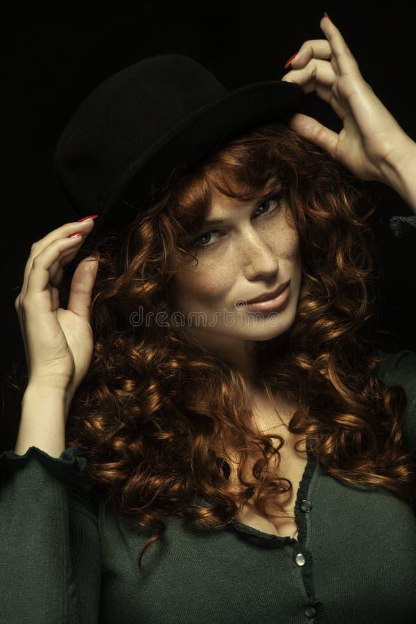 Muchacha pelirroja bastante SONRIENTE con los rizos, sombrero negro fotografía de archivo libre de regalías