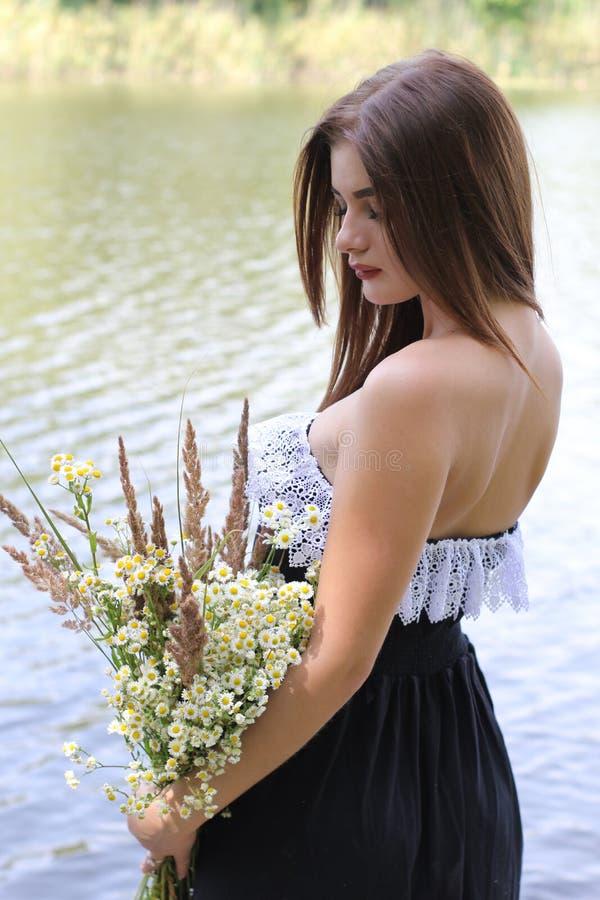 Muchacha pelirroja con un ramo de wildflowers imagen de archivo libre de regalías