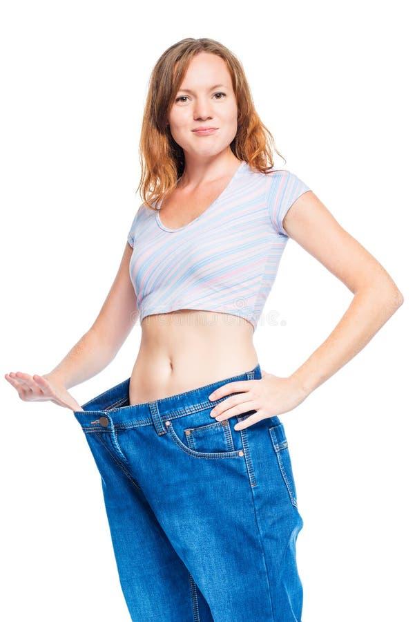 Muchacha pelirroja delgada que muestra los pantalones viejos después de peso perdidoso imagen de archivo libre de regalías