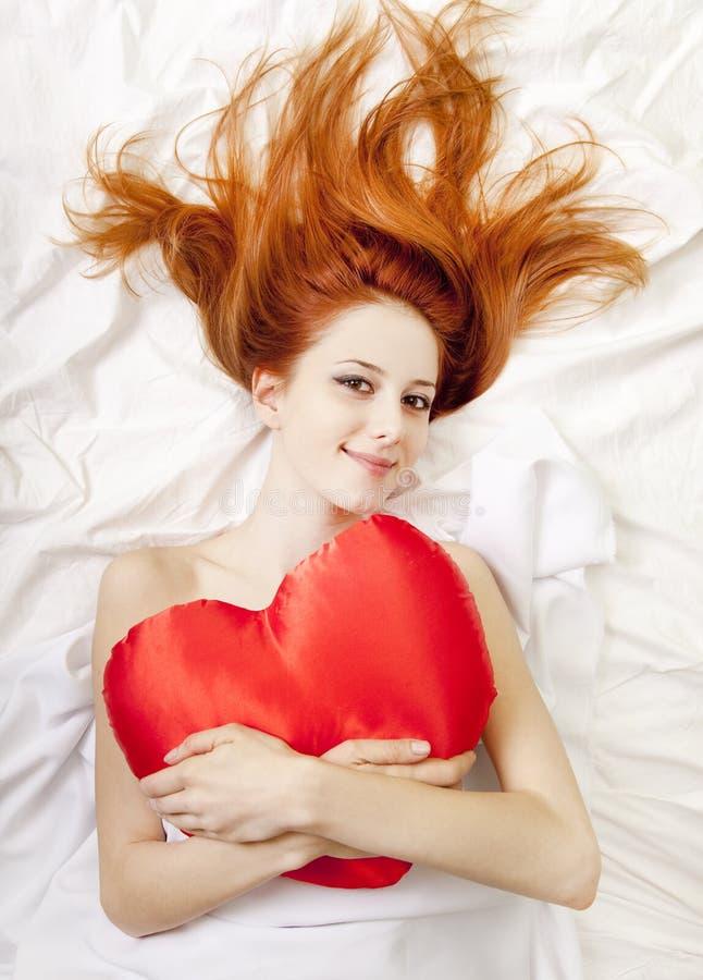 Muchacha pelirroja en cama con el corazón del juguete. imagen de archivo libre de regalías