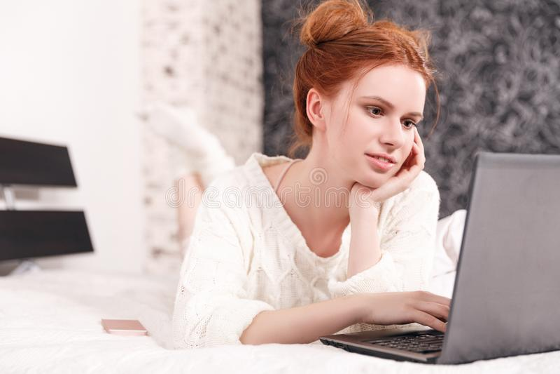 Muchacha pelirroja en la cama que trabaja en el ordenador portátil imagen de archivo