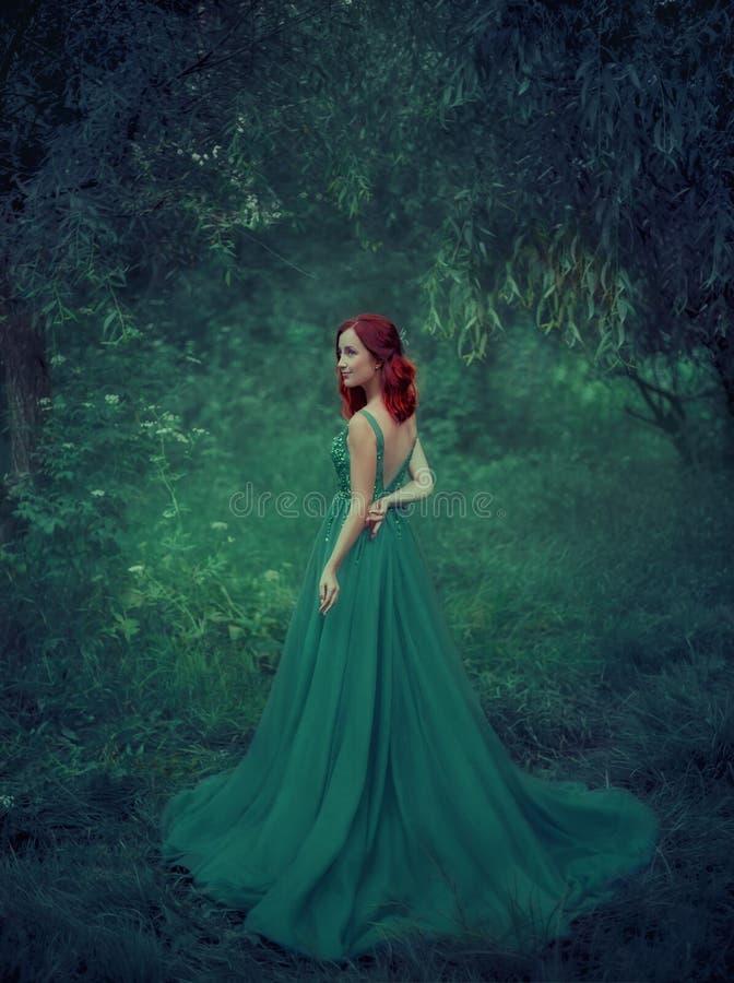 Muchacha pelirroja en un verde, esmeralda, vestido lujoso en el piso, con una espalda abierta y un tren largo La princesa fotografía de archivo