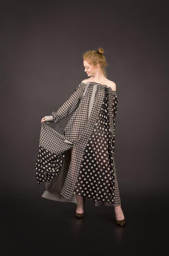 Muchacha pelirroja en un vestido largo con los hombros desnudos en un fondo oscuro foto de archivo
