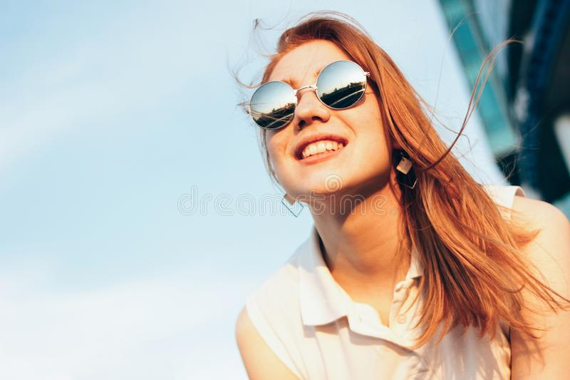 Muchacha pelirroja feliz hermosa positiva en gafas de sol del espejo en el fondo del cielo azul, tiempo de la puesta del sol del  fotografía de archivo