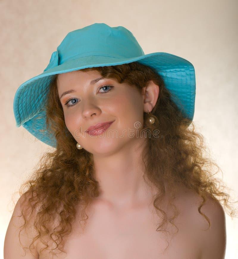 Muchacha pelirroja hermosa en un sombrero azul fotos de archivo libres de regalías