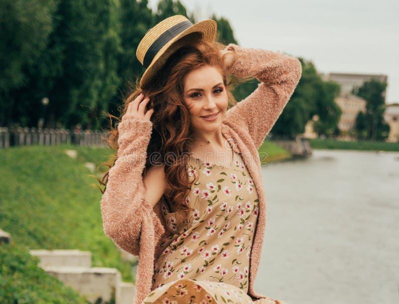 Muchacha pelirroja hermosa imagen contra la perspectiva del río, agua, lago en el parque, verano pone un sombrero en su cabeza imagen de archivo libre de regalías