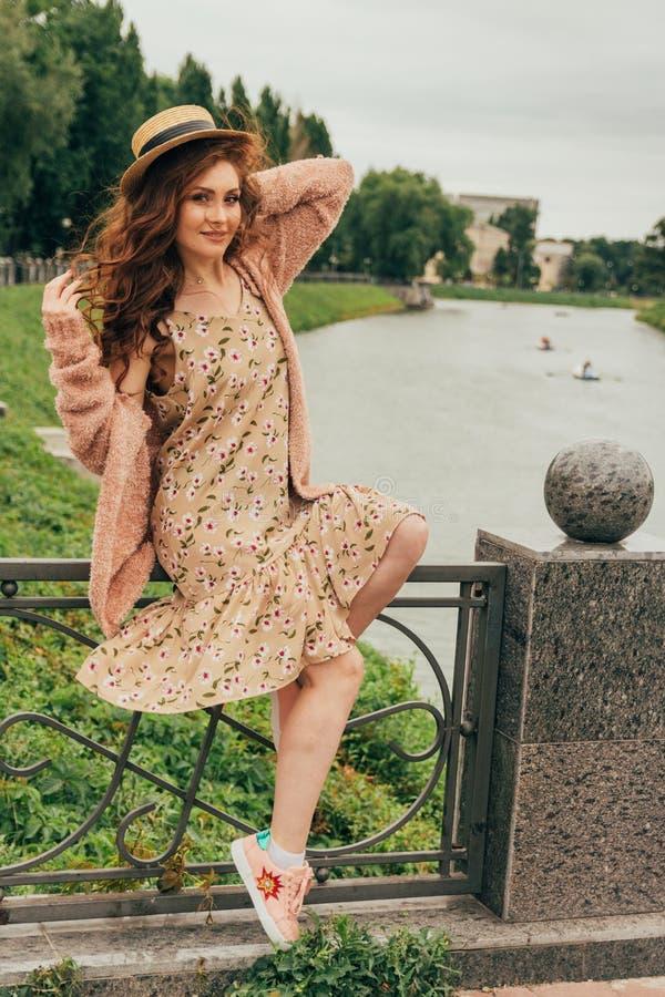 Muchacha pelirroja hermosa imagen contra la perspectiva del río, agua, lago en el parque, verano sostiene un sombrero y sonríe imágenes de archivo libres de regalías
