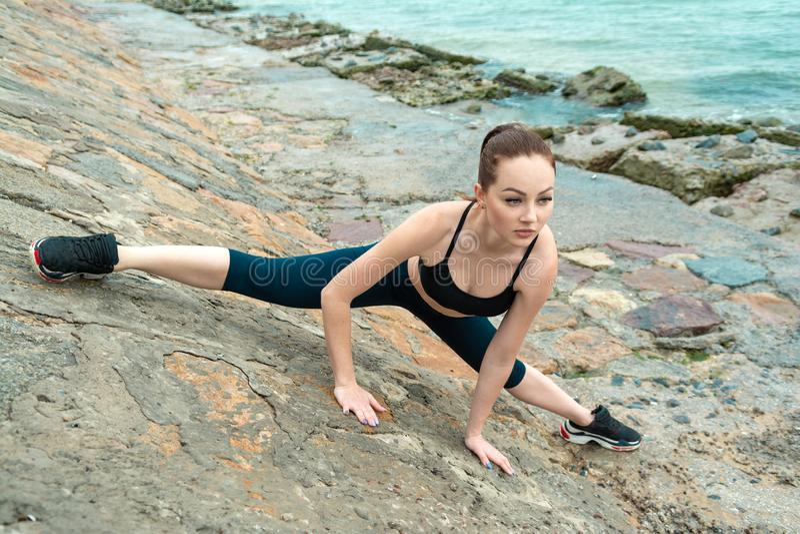 Muchacha pelirroja, joven, atl?tica, hermosa contratada en gimnasia, funcionamiento en el aire abierto Realiza los ejercicios de  imágenes de archivo libres de regalías