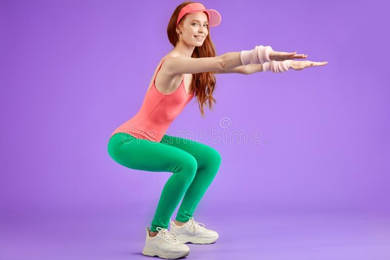 Muchacha pelirroja joven de los aeróbicos que hace ejercicios de los aeróbicos foto de archivo