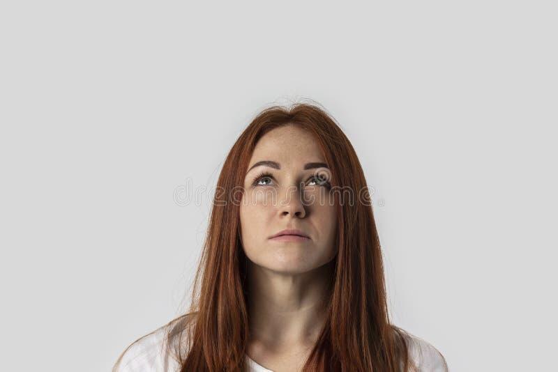 Muchacha pelirroja joven del primer aislada en fondo gris en la camiseta blanca Ella mira adentro para arriba fotos de archivo libres de regalías