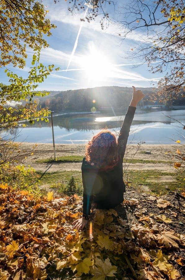Muchacha pelirroja joven que se sienta al borde del bosque imagenes de archivo