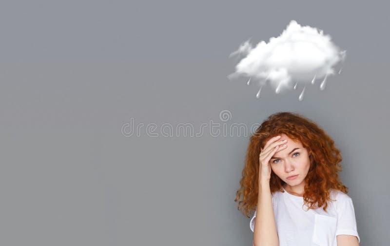 Muchacha pelirroja que lleva a cabo su cabeza con la mano debajo de la nube lluviosa fotos de archivo