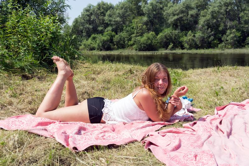 Muchacha pelirroja que miente en una colcha rosada en los bancos del río en un día soleado imagen de archivo libre de regalías