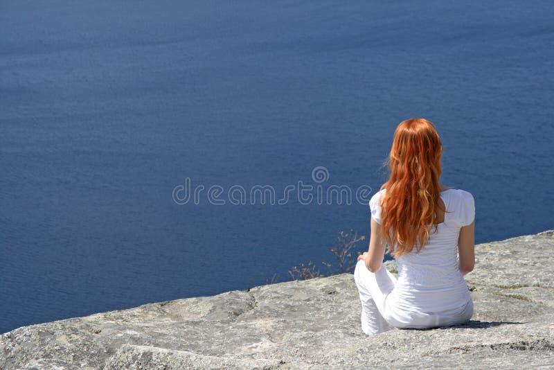 Muchacha pelirroja que mira sobre el agua azul imagen de archivo libre de regalías