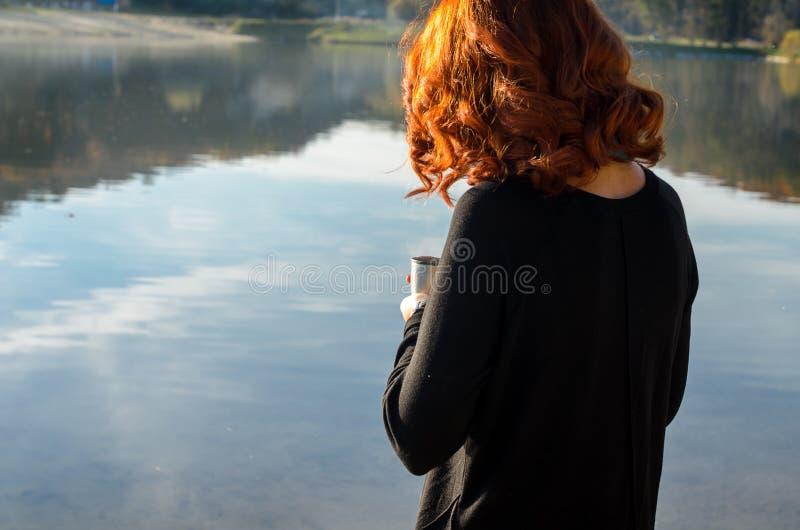 muchacha pelirroja que sostiene en sus manos a la taza del termo imagen de archivo libre de regalías