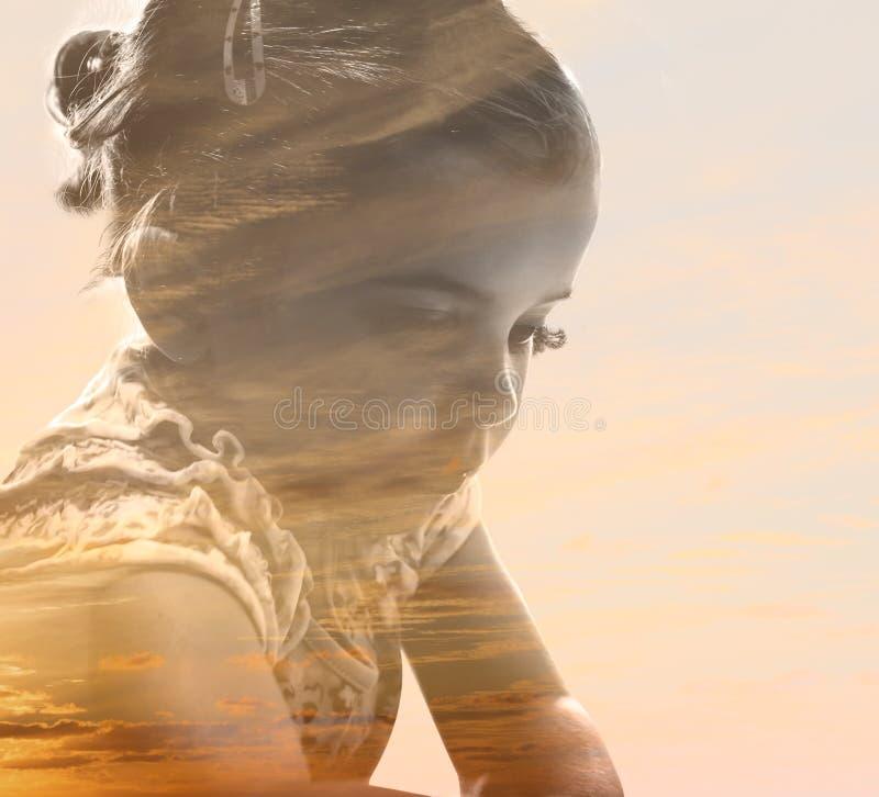 Muchacha pensativa combinada con el cielo de la puesta del sol foto de archivo libre de regalías