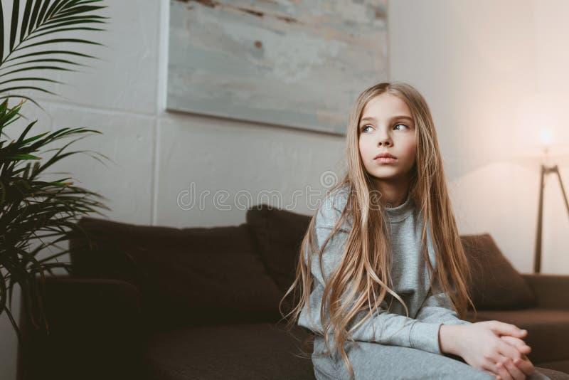 Muchacha pensativa del niño que se sienta en el sofá solamente foto de archivo libre de regalías