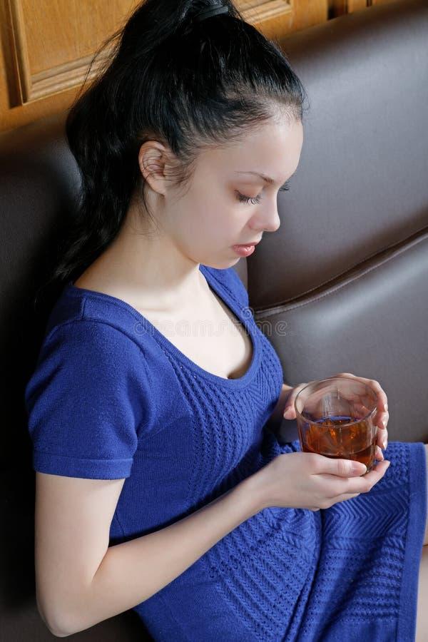 Muchacha pensativa en el sofá con un vidrio imagen de archivo