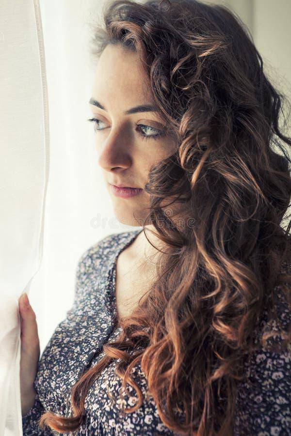Muchacha pensativa joven cerca de la cortina blanca de una ventana fotos de archivo libres de regalías