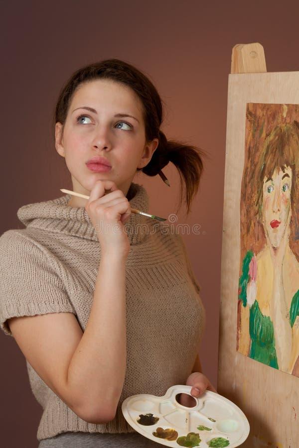 Muchacha pensativa que pinta un cuadro fotos de archivo