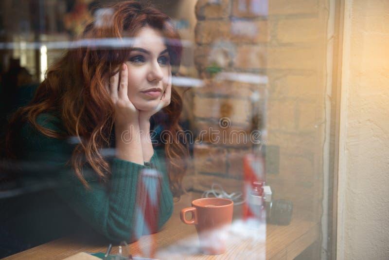 Muchacha pensativa que se sienta cerca de ventana en cafetería fotografía de archivo libre de regalías