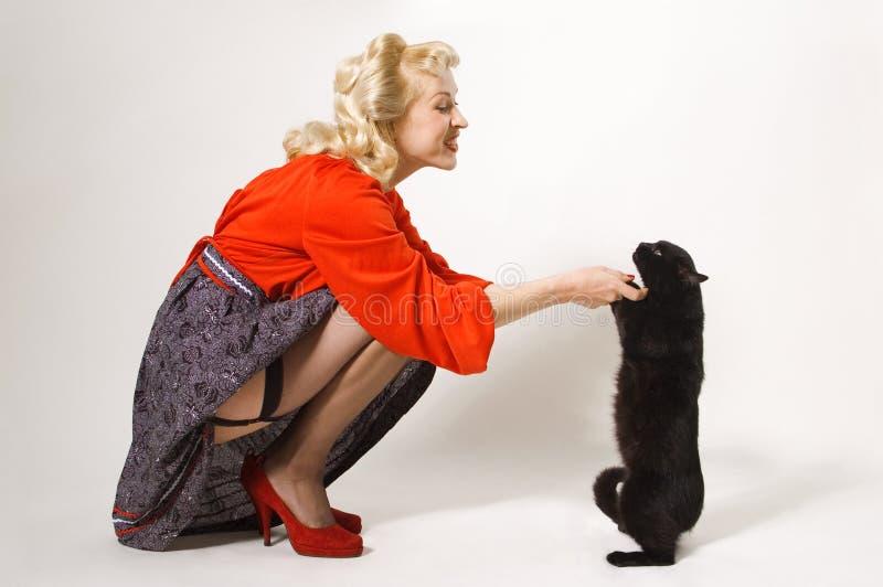 Muchacha Pin-para arriba con el gato negro fotografía de archivo