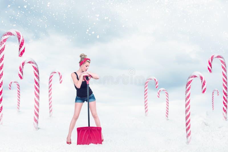 Muchacha Pin-para arriba con la pala de la nieve imagenes de archivo