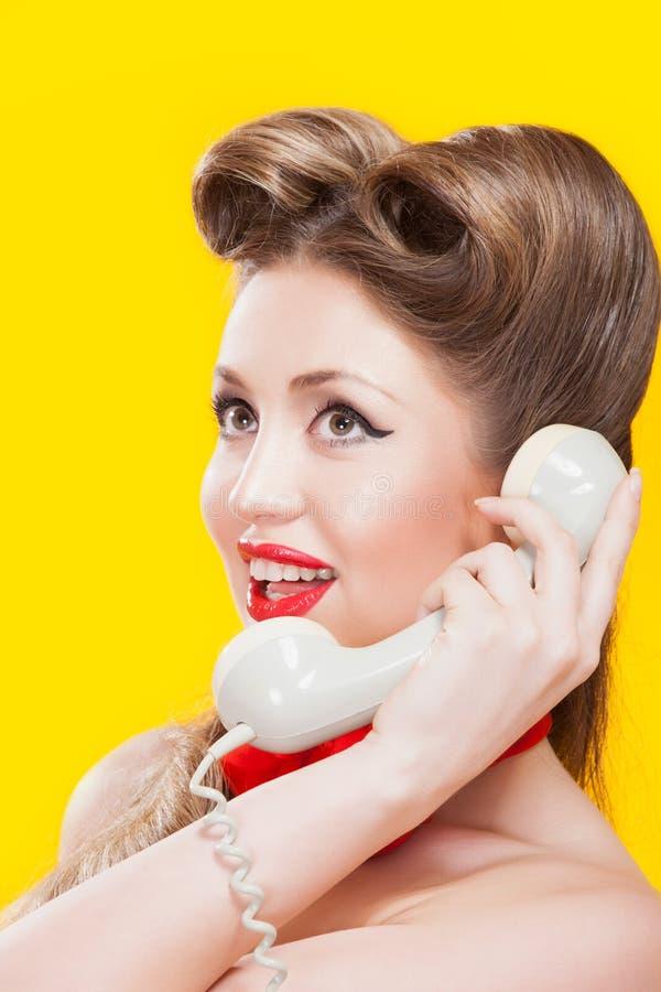 Muchacha Pin-para arriba que habla en el teléfono retro imagen de archivo