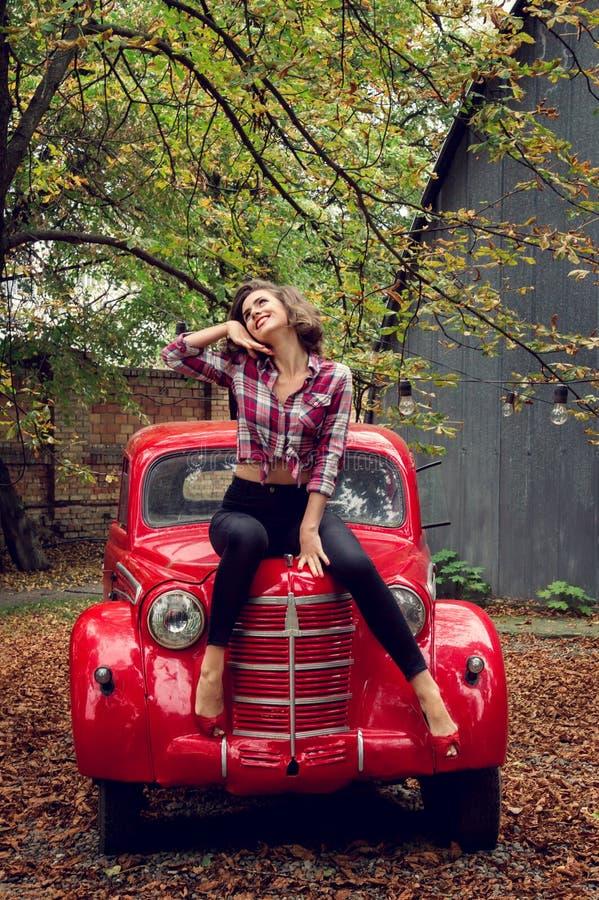 Muchacha Pin-para arriba que plantea sentarse en un coche retro ruso rojo fotos de archivo