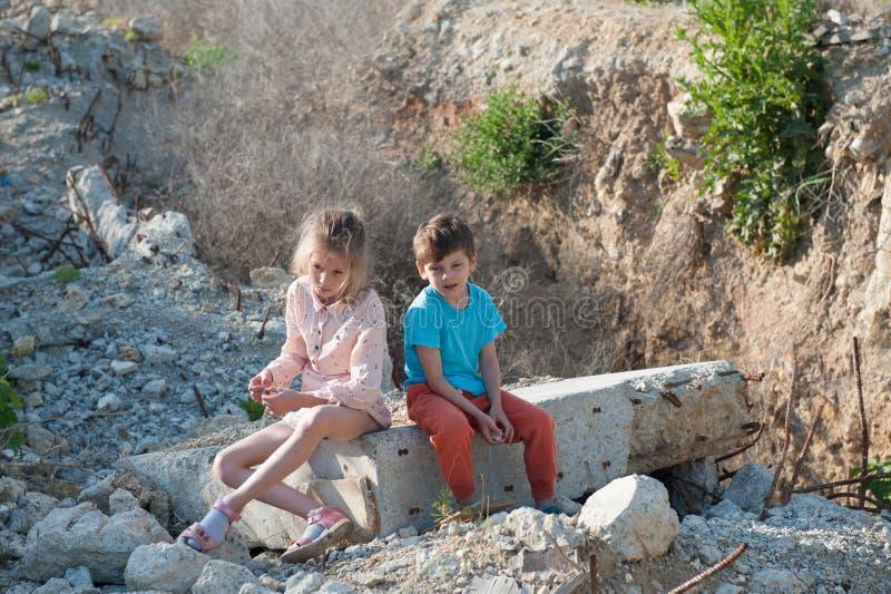 Muchacha pobre del muchacho de dos niños del refugiado en la construcción de las ruinas destruida bombardeando foto de archivo