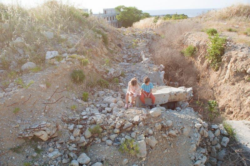 Muchacha pobre del muchacho de dos niños del refugiado en la construcción de las ruinas destruida por ataque aéreo imagen de archivo