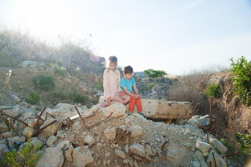 Muchacha pobre del muchacho de dos niños del refugiado en la construcción de las ruinas destruida por guerra imagen de archivo libre de regalías