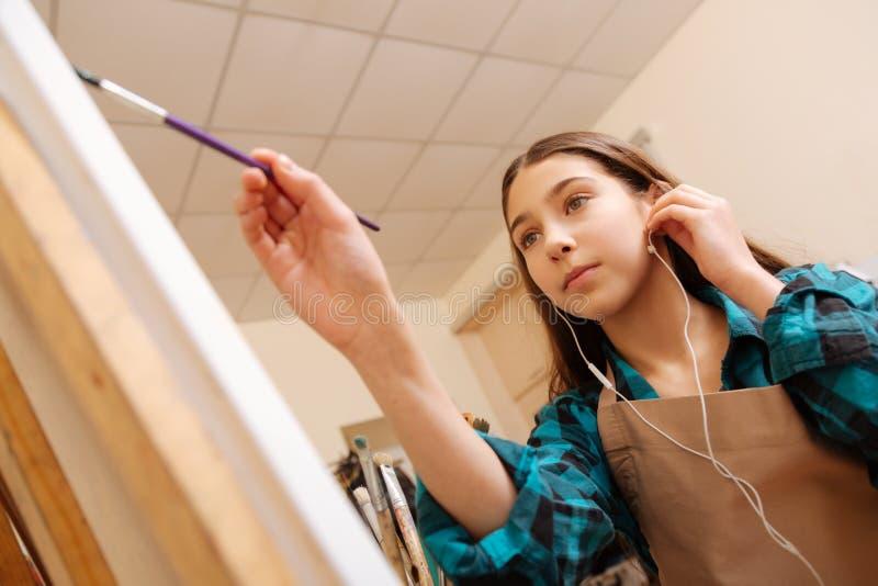 Muchacha polivalente que disfruta de la lección del arte en la escuela imagen de archivo