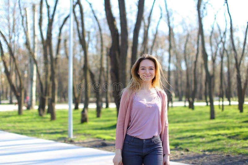 Muchacha positiva que camina en parque y la sonrisa imagen de archivo