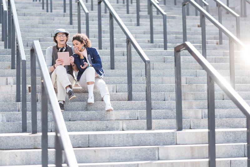 Muchacha positiva y muchacho que se sientan en pasos con sonrisa imagen de archivo
